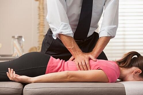 chiropractor performing a thoracic spine adjustment