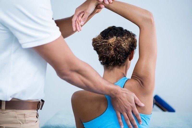 Chiropractor Adjusting Woman's Upper Back