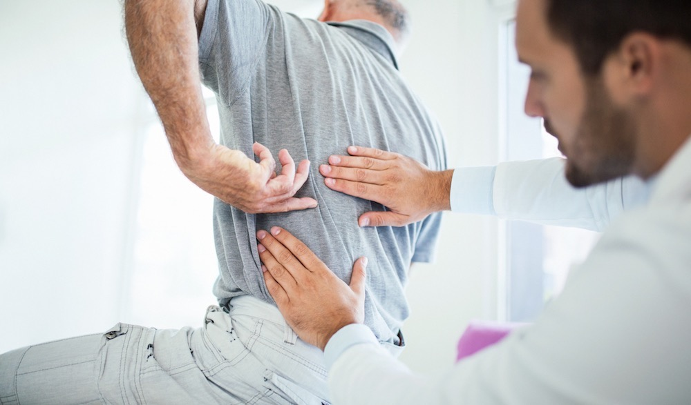 Chiropractor Adjusting a Man's Lower Back