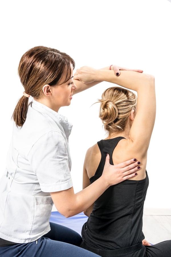 Chiropractor Adjusting Patients Back and Shoulder