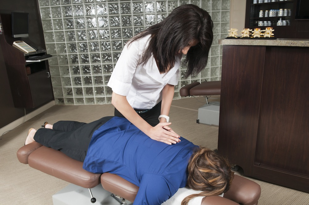 Chiropractor adjusting a patient with neck pain symptoms
